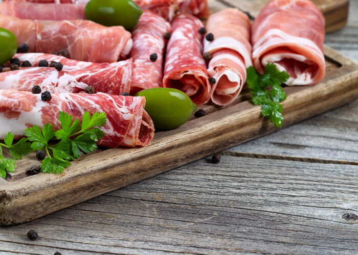 Close up horizontal image of various meats on serving board with ham pork beef parsley and olives on rustic wood. Focus on side part of serving board and first row of meat.