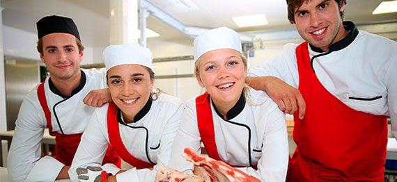 Happy team of young butchers in school kitchen
