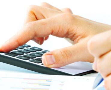 Hands of accountant with calculator and pen. Accounting background.