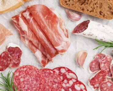Salami, sliced ham, sausage, prosciutto, bacon, toasts, olives. Meat antipasto. Top view