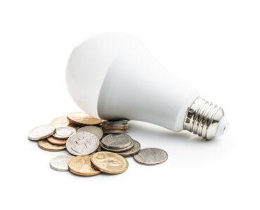 Energy saving light bulb and dollar coins isolated on white background. LED light bulb.